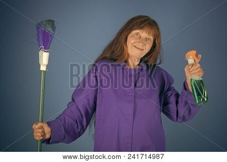 Old Lady Cleaner With Broom On Blue Background. Cleaning And Purity. Housekeeper Woman In Uniform Wi