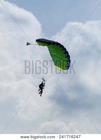 Parachutists: Instructor And Beginner With Green Parachute Preparing For Landing