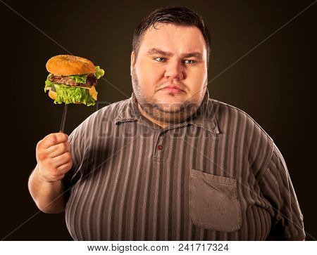 Diet failure of fat man eating fast food hamberger. Happy overweight person with wide-open mouth greedily eating huge hamburger on fork. Junk leads to obesity. He can not give up harmful food.