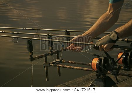 Rods, Reels, Lines And Male Hands On Water Background, Fishing. Fishing Equipment, Gear, Device. Ang