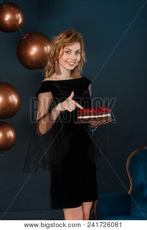 A Happy Young Woman Pointing Finger To Birthday Cake. Vertical Shot On Black Background.
