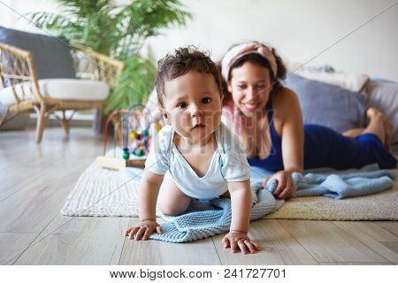 Adorable 6 Month Old Toddler Learning How To Crawl On Floor, His Young Smiling Mom In Background. He