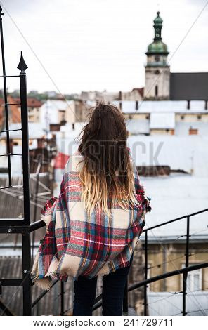 Beautiful Young Girl Is Standing On The Roof And Looking At The City A