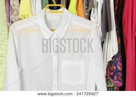 White Transparent Blouse On Hanger In Front Of Other Female Clothes In The Closet