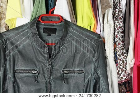Green Leather Jacket In Front Of Other Female Clothing