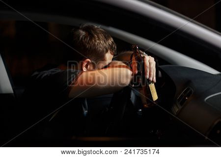 Male Drunk Driver Drinking Beer On The Background Of Police Car Lighting. Driving Under Alcohol Infl