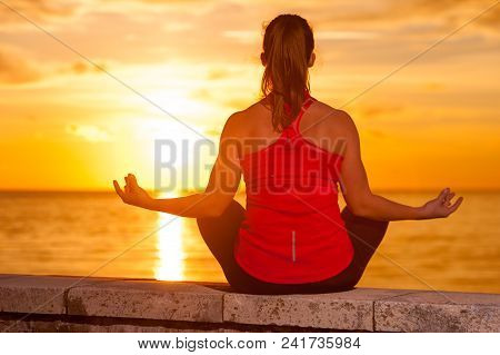 Rear View - Silhouette Of Relaxed Woman Sitting In Yoga Meditation Pose Against Background Of Sea Su