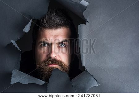 Serious Bearded Man Peeping Through Black Paper Hole. Attractive Man With Beard&mustache Breaking Pa