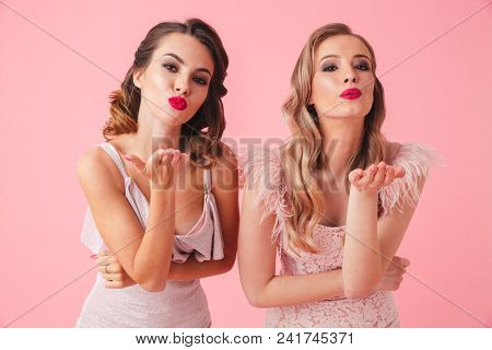Two lovely women in dresses sends air kisses and looking at the camera over pink background