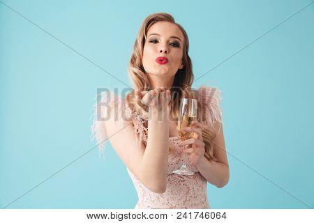 Sensual pleased blonde woman in dress posing with champagne and sends air kiss at camera over turquoise background