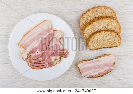 Sandwich With Bacon, Pieces Of Bread, Plate With Bacon On Wooden Table. Top View