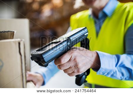 Unrecognizable Warehouse Woman Worker Or Supervisor Using A Mobile Handheld Pc With Barcode Scanner.