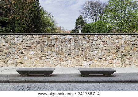 Two Stone Benches On The Sidewalk Of A Street In A City Next To A Park