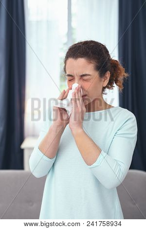Nose congestion. Young slender sick-looking woman staying at home and cleansing up her congested nose while having her eyes closed poster