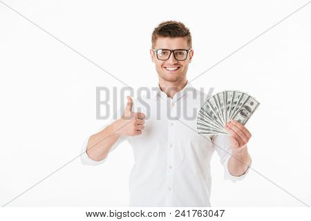 Portrait of a confident young man in eyeglasses holding money banknotes and showing thumbs up isolated over white background