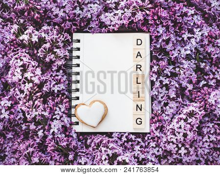 Heart-shaped cookie, covered with bright glaze, word DARLING, sketchbook with a blank page for Your inscription on the background flowers. Top view, close-up. Congratulations for relatives, loved ones poster