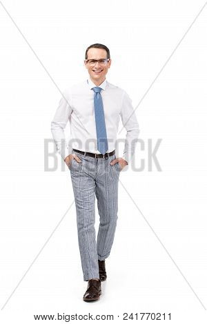 Handsome Adult Businessman With Hands In Pockets Walking At Camera Isolated On White