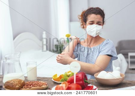Egg Allergy. Young Woman Wearing A Respiratory Mask Displaying Symptoms Of A Severe Egg Allergy Affe