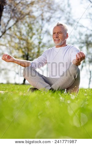 Peace Of Mind. Cheerful Aged Man Sitting In The Lotus Pose While Meditating
