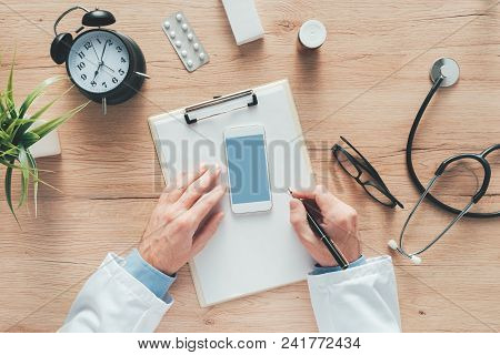 Male Doctor Writing Notes On Clipboard Paper During Medical Exam