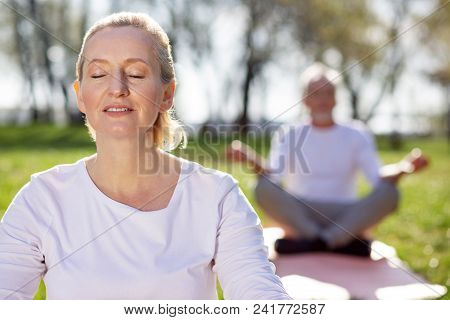 Absolute Calmness. Pleasant Aged Woman Closing Her Eyes While Feeling Absolutely Calm