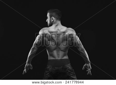 Unrecognizable Man Bodybuilder Shows Strong Hands And Back Muscles, Athletic Trapezius, Black And Wh