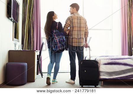 Young Happy Couple With Luggage In Hotel Room. Just Married Man And Woman Arrived To Resort, Romanti