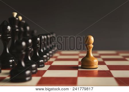 One pawn standing against set of black chess. Alone against many enemies, symbol of difficult fight or struggle, confidence concept poster