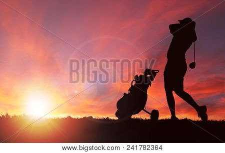 Silhouette Of Golfer With Golf Bag By His Side Swinging Club Toward Sunset With Deliberate Lens Flar
