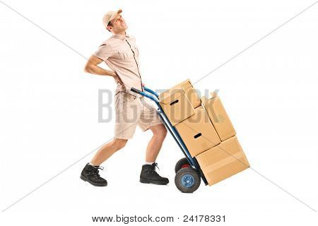 Full length portrait of a delivery boy, suffering from a back pain, pushing a hand truck isolated on white background