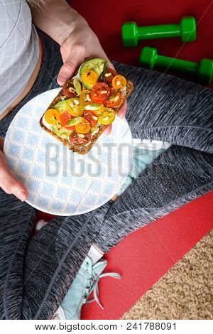 Girl Sportswoman Sitting On A Rug Next To A Dumbbell And Holding A Bruschetta With Avocado, Cherry T