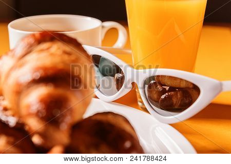 Hat, Sunglasses Croissant With A Cup Of Coffee And A Glass Of Orange Juice On A Yellow Table In The
