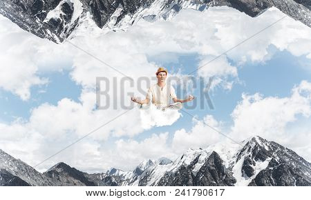 Young Man Keeping Eyes Closed And Looking Concentrated While Meditating On Cloud In The Air Between