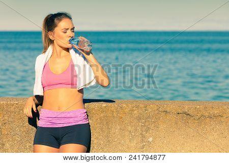 Woman In Sportswear Takes A Break To Rehydrate Drinking Water From Plastic Bottle, Resting After Spo