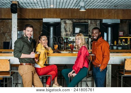 Group Of Young Friends With With Various Alcohol Beverages Spending Time Together In Bar