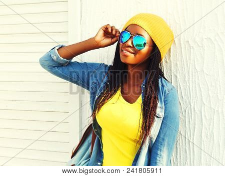 African Woman With Skateboard In Colorful Clothes And Sunglasses Outdoors