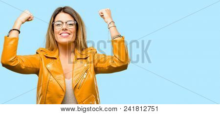 Beautiful young woman showing biceps expressing strength and gym concept, healthy life its good