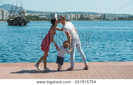 Kiss Of Happy Couple With Child Son. Kiss And Love Concept