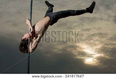 Strong Man Dancer Workout On Pole In Sunset. Sexy Macho Man Fly. Young Muscular Man Dancing On Pylon