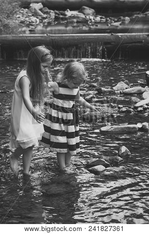 Innocence, Purity And Youth Concept. Girls Walk On Stones In Water Stream At Waterfall. Children Pla