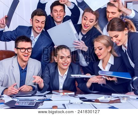 Business people office life of team people are happy with hand up sitting table and working papers. Cabinets with folders and jalousie background. Welcome reception at bank.