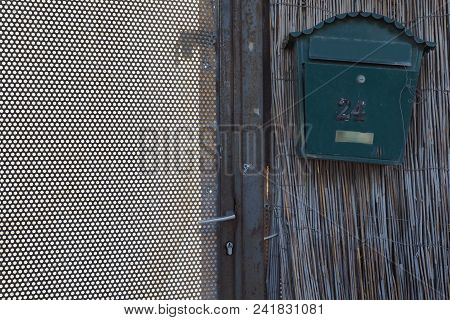 Vintage Metallic Green Mailbox On A Bamboo Wall, On The Left A Metal Grille With Round Holes.