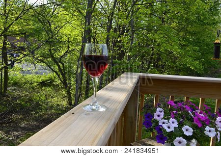 Red Wine In A Glass On The Outdoor Deck Railing With A Green Nature Background And Flowers