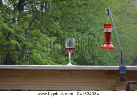 Red Wine In A Glass On The Outdoor Deck Railing With A Green Nature Background And A Hummingbird Fee