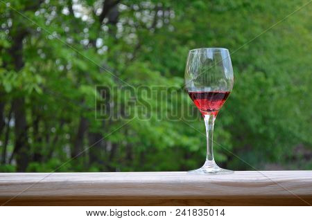 Red Wine In A Glass On The Outdoor Deck Railing With A Green Nature Background