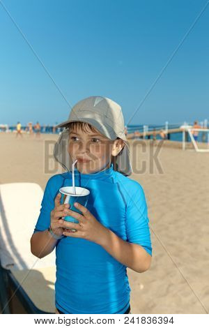Summer portrait of cute little boy on the beach, drinking.