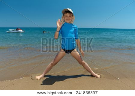 Cute little boy playing on the beach, waving, smiling.
