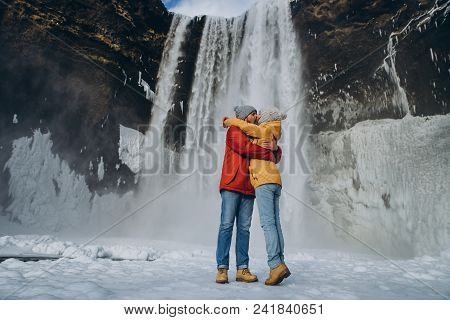 beautiful young couple hugging and kissing near majestic skogafoss waterfall in iceland poster