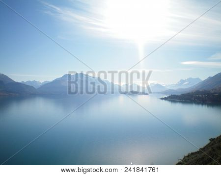 A Still Blue Lake Surrounded By Mountains. Snow Is On A Few Of Them. There Is A Blue Sky With White