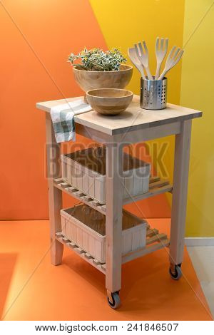 Wooden Island Kitchen Cart For Home Design And Decoration Against Yellow Wall.